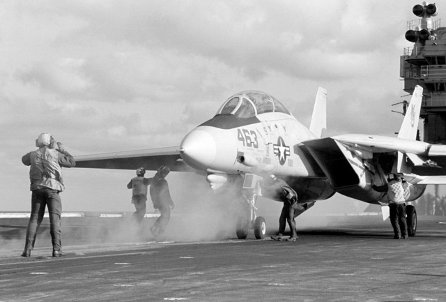 A plane director guides an F-14A Tomcat aircraft onto a catapult during flight operations aboard the aircraft carrier USS CONSTELLATION (CV 64)