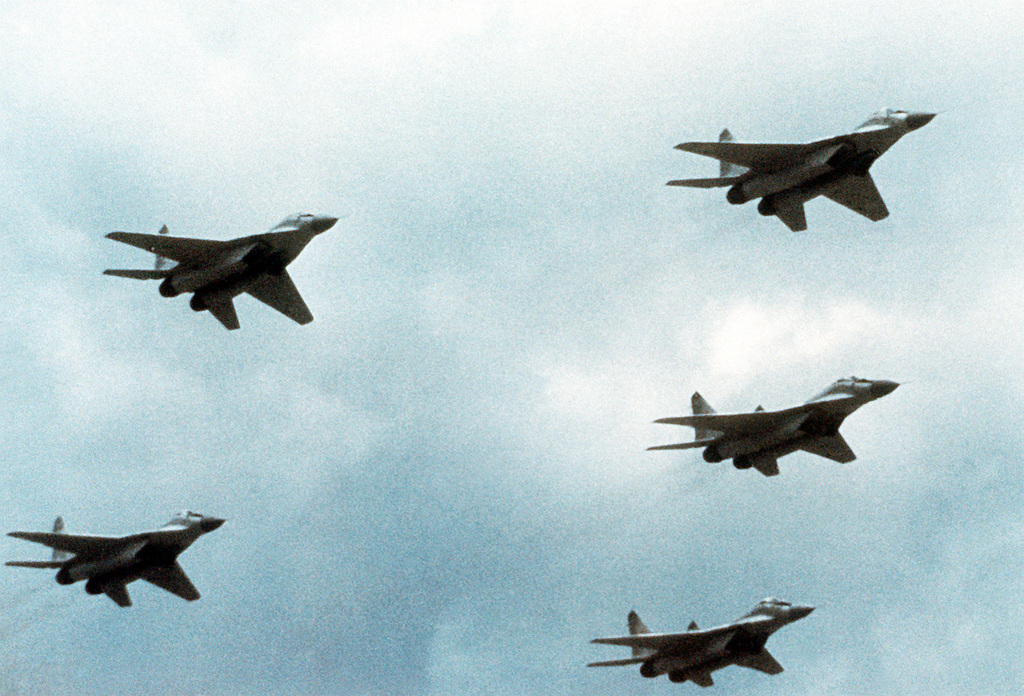 A right underside view of five Soviet MiG-29 Fulcrum aircraft flying in formation
