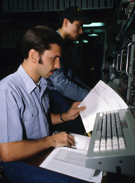 A sailor examines a printout from a teletype machine in a communications center aboard the aircraft carrier USS KITTY HAWK (CV 63)