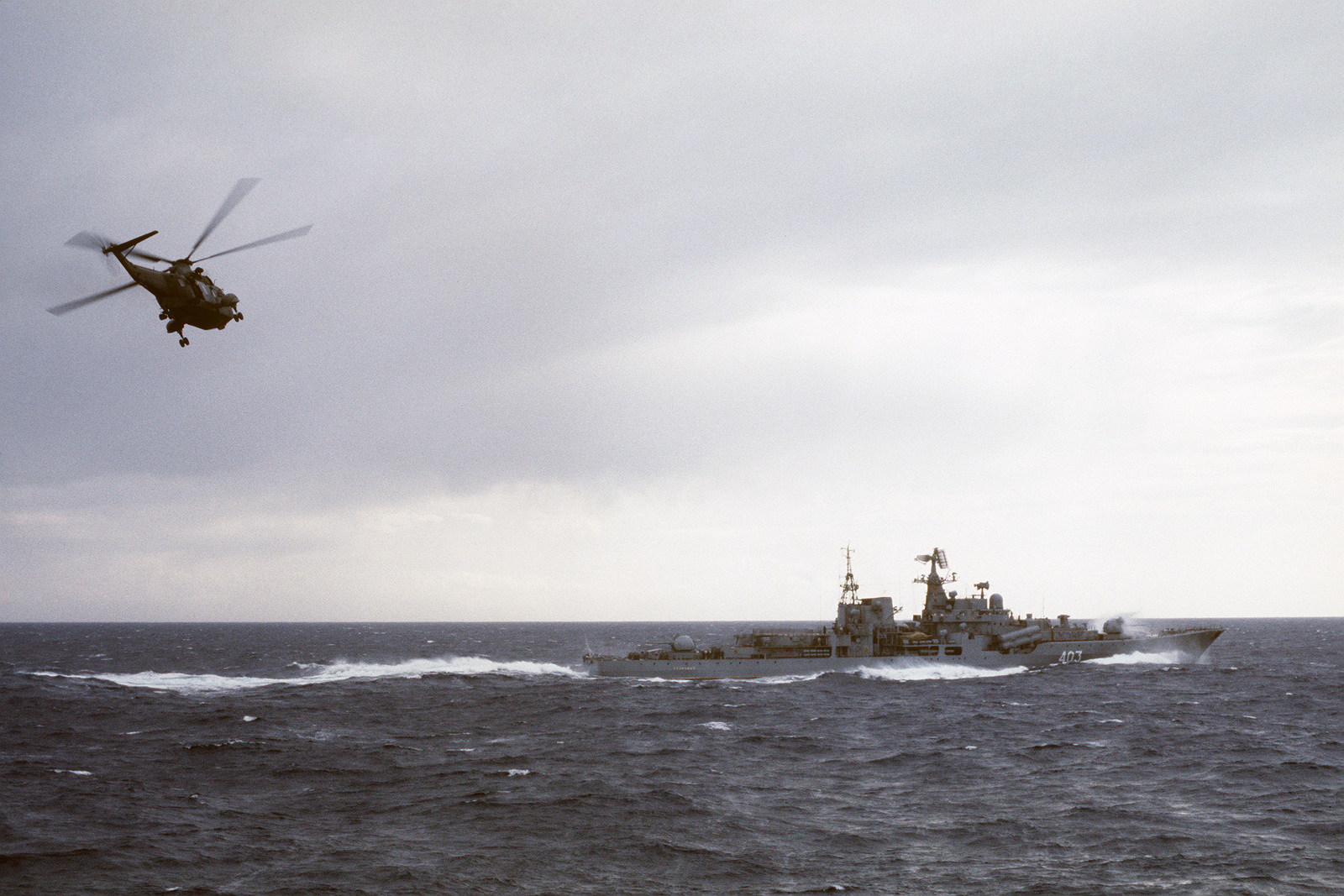 A starboard view of a Soviet Sovremennyy class guided missile destroyer underway as a US Navy SH-3 Sea King helicopter approaches the ship