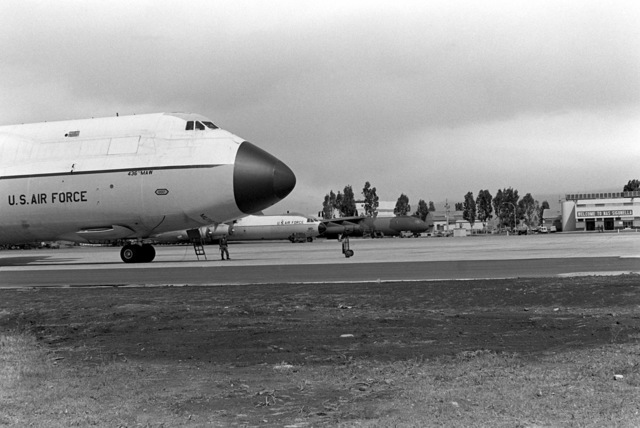 A US Air Force C-5A Galaxy aircraft, background, and two Air Force C-141B Starlifter aircraft sit on the flight line during a stopover at the air station
