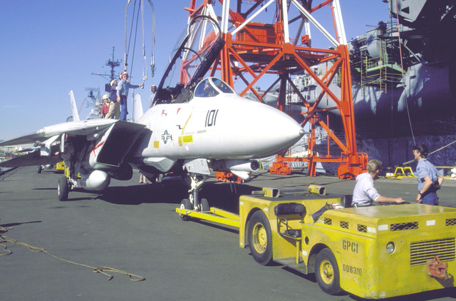 Am MD-3A tow tractor is used to maneuver a Fighter Squadron 211 (VF-211) F-14A Tomcat aircraft into position prior to being hoisted by crane aboard the aircraft carrier USS KITTY HAWK (CV-63)