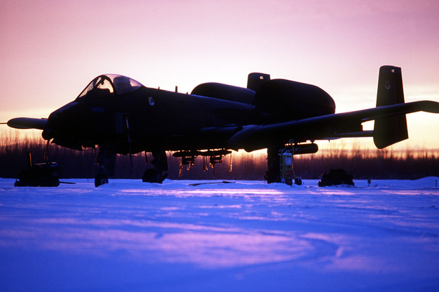 An A-10 Thunderbolt II aircraft from the 343rd Tactical Fighter Wing is silhouetted by the sun as it stands parked on an icy flight line at sunrise during exercise Brim Frost '87