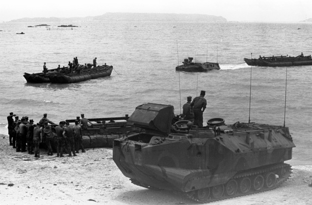 An AAV-7 assault amphibian vehicle of Company A, 2nd Assault Amphibian Battalion, tows a section of bridging as another AAV-7 and a bridging section are positioned on the beach. The sections of bridging are being connected to form a ferry during a bridging exercise off Kin Blue Beach. Marines of Co. B, 9th Engineer Support Bn., 3rd Force Service Support Grp., are also participating in the exercise