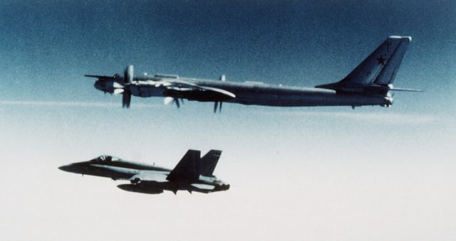 An air-to-air left side view of a Soviet Bear H bomber aircraft alongside a Canadian CF-18 Hornet aircraft