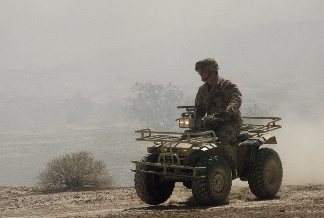 An airman surveys the area using an all-terrain vehicle during Silver Flag Alpha, a security police training program emphasizing combat arms training and defense of priority resources on an air base