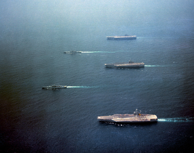 An elevated port beam view of the nuclear-powered aircraft carriers USS NIMITZ (CVN 68), back row, bottom, USS DWIGHT D. EISENHOWER (CVN 69), center, and USS CARL VINSON (CVN 70), top, underway.  Leading the carriers are the nuclear-powered guided missile cruisers USS VIRGINIA (CGN 38), front row, top, and USS SOUTH CAROLINA (CGN 37) in the Virginia Capes