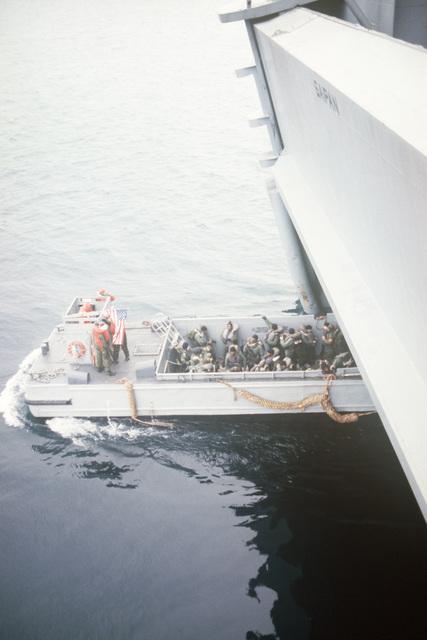 An LCM 6 mechanized landing craft backs out of the docking well of the amphibious assault ship USS SAIPAN (LHA 2)
