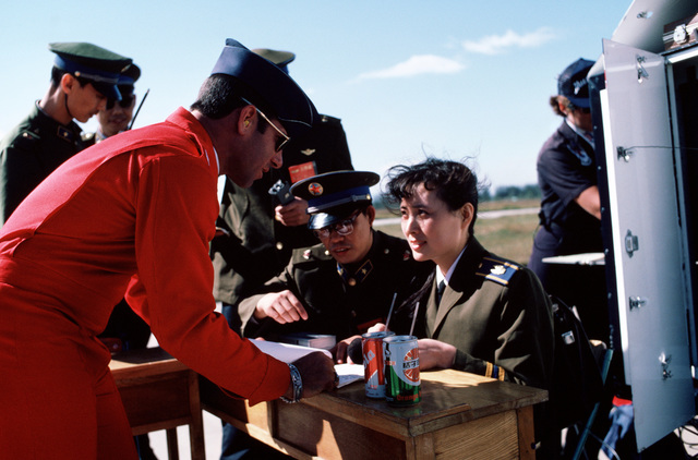 Captain (CPT) Bert Nelson, narrator for the US Air Force Thunderbirds flight demonstration team, reviews his script with a Chinese translator prior to a team performance.  The Thunderbirds are performing in China as part of their 1987 Pacific tour which e