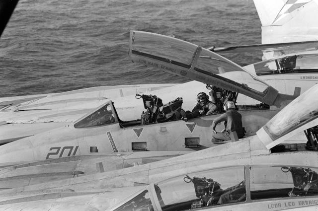 Flight deck crewmen work in the cockpit of an F-14A Tomcat aircraft parked on the flight deck of the aircraft carrier USS JOHN F. KENNEDY (CV 67)