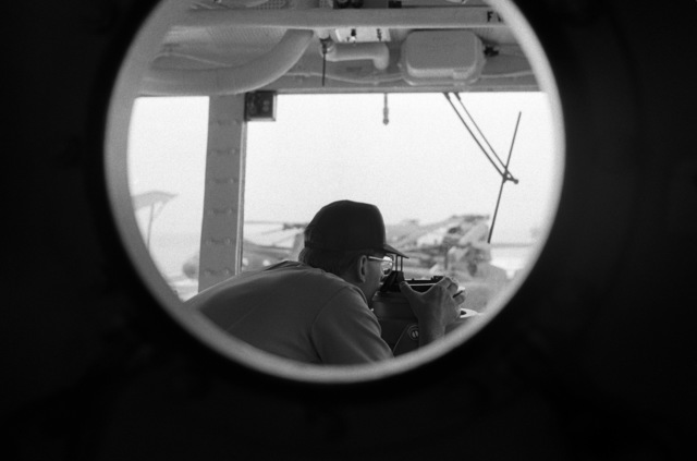 Framed by a pothole, an officer sights through an azimuth circle on the bridge of the amphibious assault ship USS TRIPOLI (LPH 10). The TRIPOLI is acting as a command ship for US forces during Exercise VALIANT USHER '87, a joint military exercise with Royal Australian forces