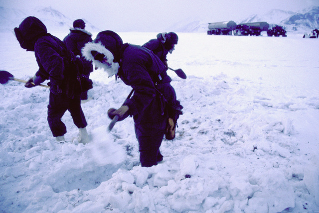 Members of the 722nd Combat Control Squadron and the 616th Combat Control Group dig out a level place in the snow for their tents during exercise Brim Frost '87