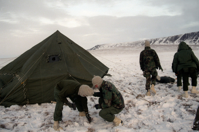 Members of the 722nd Combat Control Squadron secure tent stakes in the snow during exercise Brim Frost '87