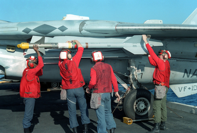 Ordnancemen mount an AIM-9 Sidewinder missile onto a Fighter Squadron 102 (VF-102) F-14A Tomcat aircraft parked on the flight deck of the nuclear-powered aircraft carrier USS THEODORE ROOSEVELT (CVN 71)