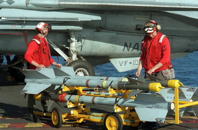 Ordnancemen prepare to mount AIM-9 Sidewinder missiles on a Fighter Squadron 102 (VF-102) F-14A Tomcat aircraft parked on the flight deck of the nuclear-powered aircraft carrier USS THEODORE ROOSEVELT (CVN-71)
