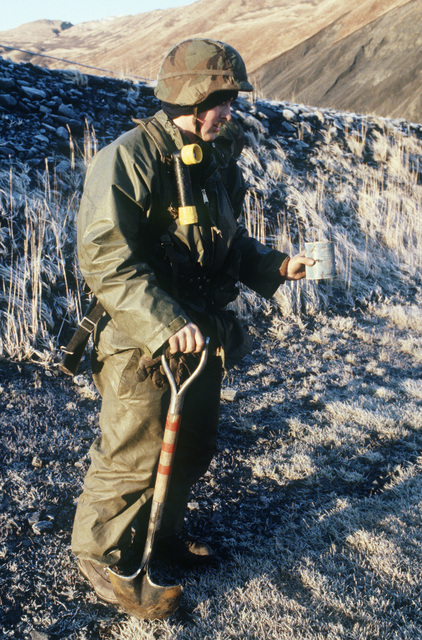 Private First Class (PFC) Jerry Bogohn, 562nd Engineer Battalion, digs up an anti-personnel mine from the ramp area of the air strip during Exercise BRIM FROST'87