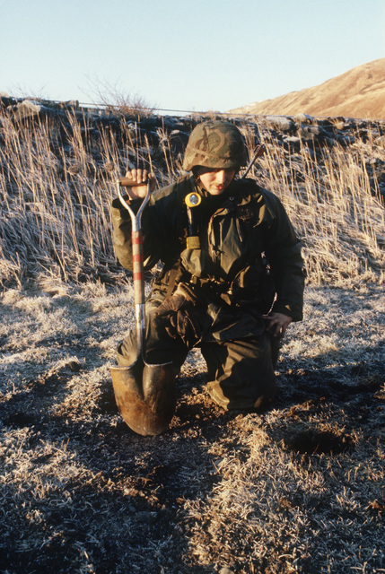 Private First Class (PFC) Jerry Bogohn, 562nd Engineer Battalion, digs up an anti-personnel mine from the ramp of the air strip during Exercise BRIM FROST'87