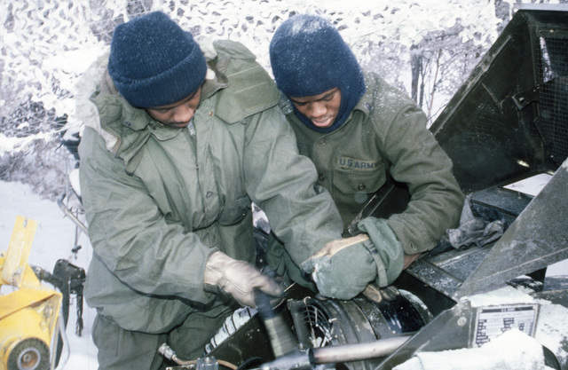 Private First Class (PFC) John Walton and Specialist Fourth Class (SPC) James Austin, 172nd Support Battalion 6th Infantry Division, repair heater attached to a maintenance tent during Exercise BRIM FROST'87