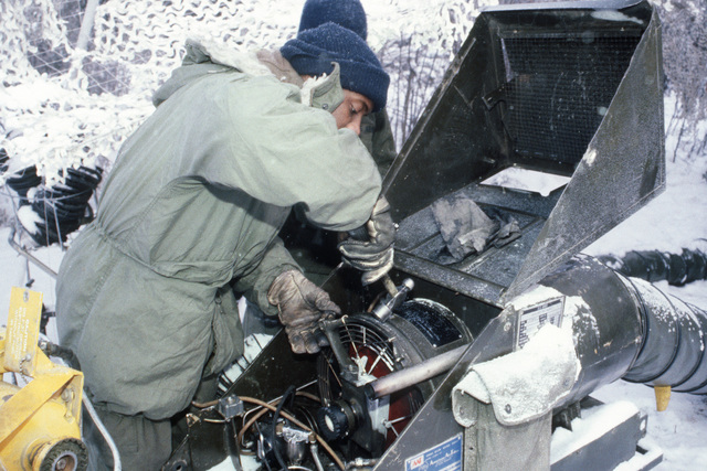 Private First Class (PFC) John Walton and Specialist Fourth Class (SPC) James Austin, 172nd Support Battalion 6th Infantry Division, repair a heater attached to a maintenance tent during Exercise BRIM FROST'87