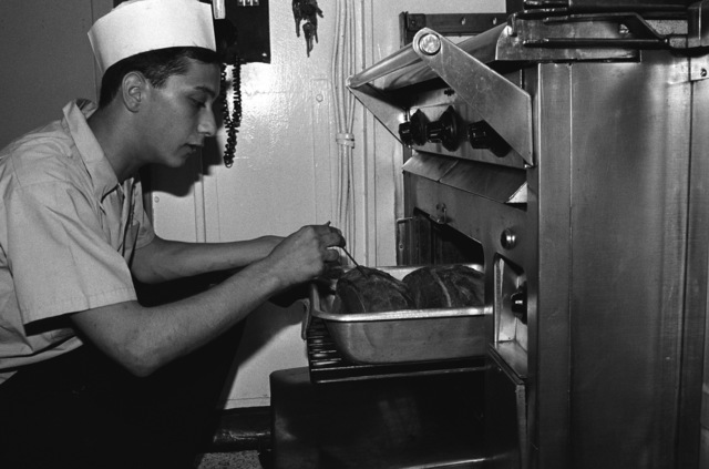 SEAMAN (SN) John Wakeen, mess management specialist on the staff of Commander Amphibious Squadron 5, takes the temperature of a roast in the commander's galley aboard the amphibious assault ship USS TRIPOLI (LPH 10). The TRIPOLI is acting as a command ship for US forces during Exercise VALIANT USHER '87, a joint military exercse with Royal Australian forces