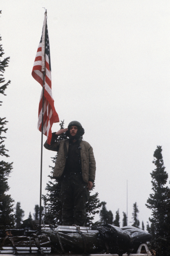 Sergeant (SGT) Peter Mishou salutes a flag he has raised on the antenna of an M113A1 armored personnel carrier during moring formation.  SGT Mishou dedicated the formation to the memory of friends who died in Vietnam and will hoist a flag that flew in battle during the war.  The sergeant's squad is participating in Exercise BRIM FROST'87