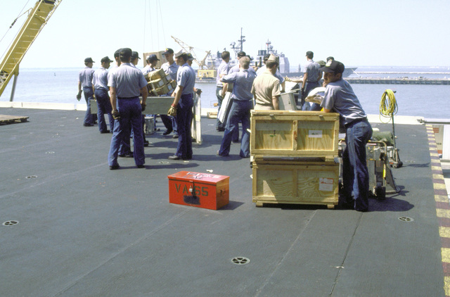 Shipyard workers and crew members remove supplies and cargo being transported by pierside conveyer onto the flight deck of the aircraft carrier USS KITTY HAWK (CV-63)