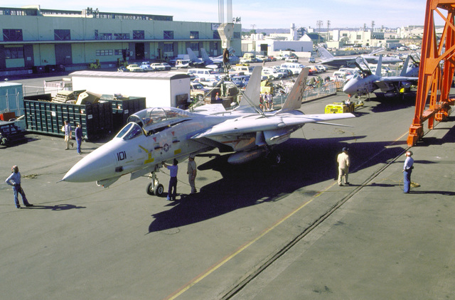 Shipyard workers check stabilizing ropes tied to the landing gear of a Fighter Squadron 211 (VF-211) F-14A Tomcat aircraft as it is hoisted by crane aboard the aircraft carrier USS KITTY HAWK (CV-63)