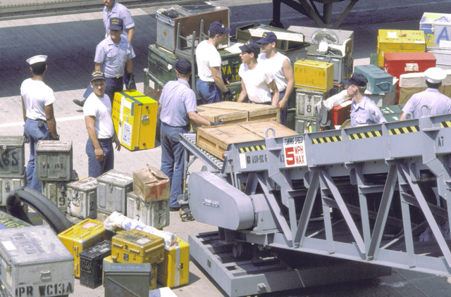 Shipyard workers use a pierside conveyer to transport supplies and cargo to the aircraft carrier USS KITTY HAWK (CV-63)