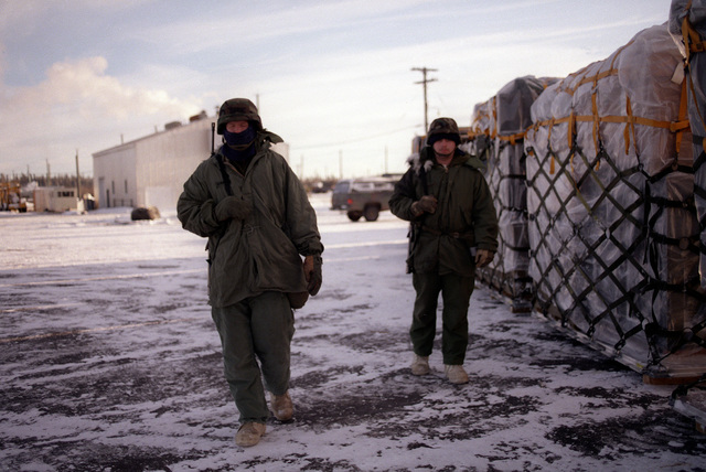 Spec. 4 Eric Strawsine and Spec. 4 James Wilbanks, 172nd Security Police Battalion, patrol the cargo area at Allen Army Airfield during exercise Brim Frost '87