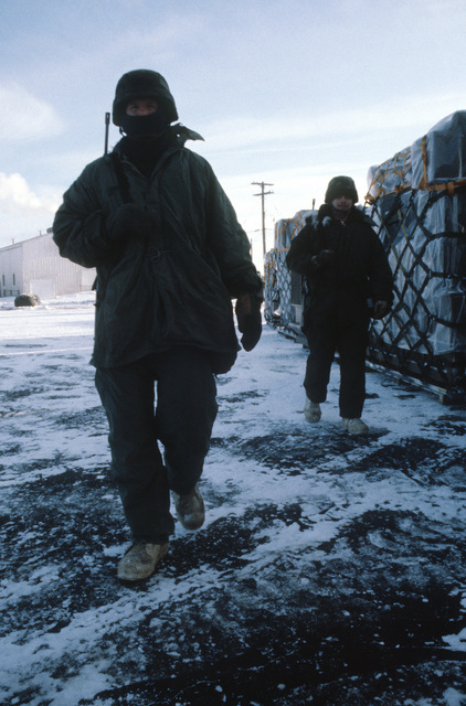 Specialist 4 (SPC) Eric Strawsine and James Wilbanks patrol the cargo area at Allen Army Air Field during Exercise BRIM FROST'87