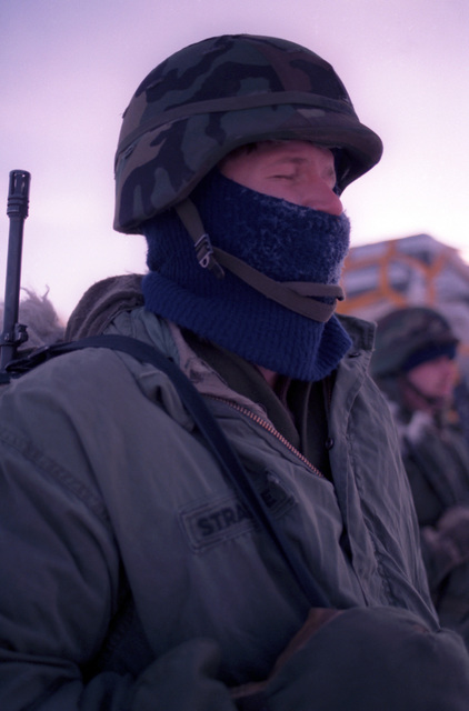 Specialist Fourth Class (SPC) Eric Strawsine, 172nd Security Police Battalion, stands guard at the Allen Army Airfield cargo area during Exercise BRIM FROST'87