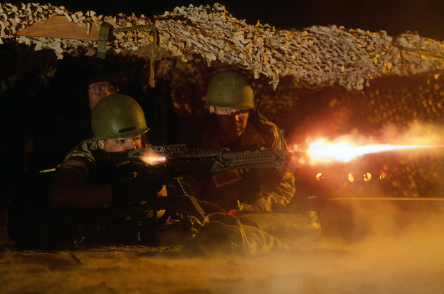 SRA J.D. Lough fires an M-60 machine gun as SGT Robert W. Dixon II assists during a night firing exercise. The men are taking part in Silver Flag Alpha, a security police training program emphasizing combat arms training and defense of priority resources on an air base