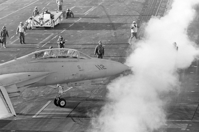 Steam rises from a catapult as a Naval Air Reserve Fighter Squadron 301 (VF-301) F-14A Tomcat aircraft is moved into position for launch during flight operations aboard the aircraft carrier USS CONSTELLATION (CV 64)