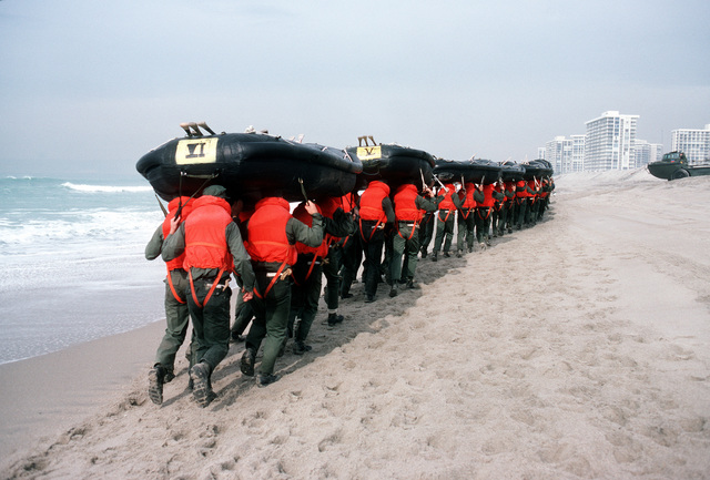 Students carry rubber rafts while marching along Coronado Beach during Basic Underwater Demolition/SEAL (BUD/S) training
