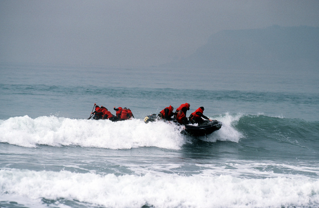 Students struggle through the surf in rubber rafts during Basic Underwater Demolition/SEAL (BUD/S) training