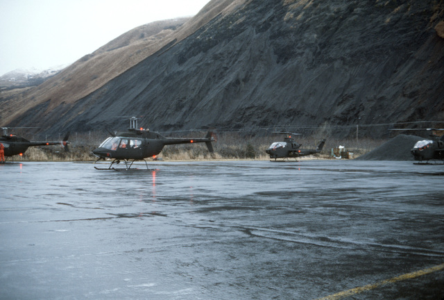 Two AH-1 Cobra and two OH-58 Kiowa helicopters prepare for takeoff during Exercise BRIM FROST'87