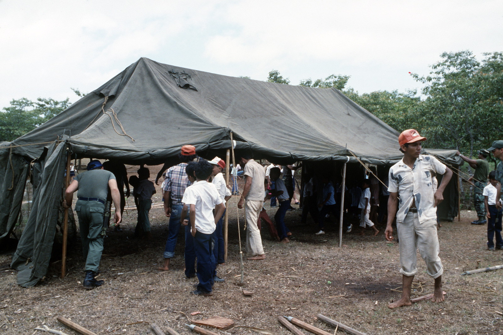 Villagers gather at a camp tent during a medical exercise