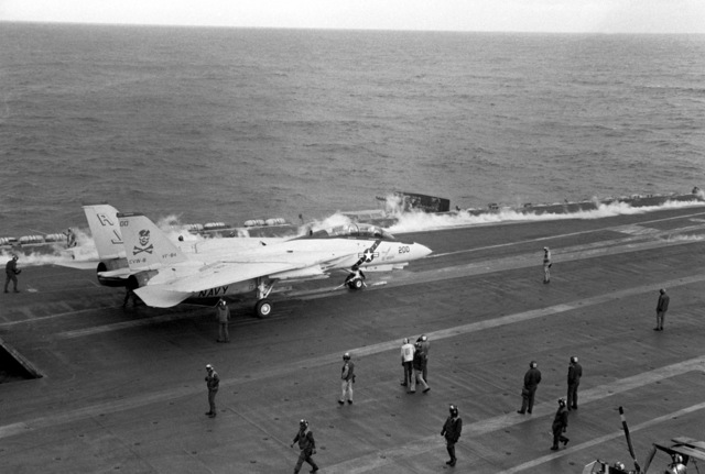 With steam still rising from the tracks of the No. 4 waist catapult following the launch of an aircraft, a Fighter Squadron 84 (VF-84) F-14A Tomcat aircraft waits for launch on the No. 3 waist catapult aboard the nuclear-powered aircraft carrier USS NIMITZ (CVN 68)