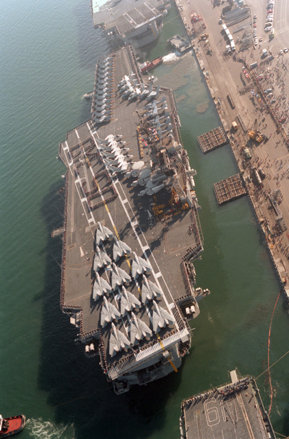 """Crew members spell out """"BYE SD"""" on the flight deck of the aircraft carrier USS KITTY HAWK (CV 63) as large harbor tugs move it away from its moorings at Naval Air Station, North Island. The KITTY HAWK has been reassigned to the Atlantic Fleet"""
