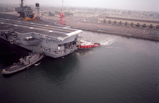 The large harbor tug CANONCHET (YTB 823) works with a smaller tug to move the stern of the aircraft carrier USS KITTY HAWK (CV 63) away from its moorings at Naval Air Station, North Island. The KITTY HAWK is getting underway for the East Coast after being reassigned to Atlantic Fleet