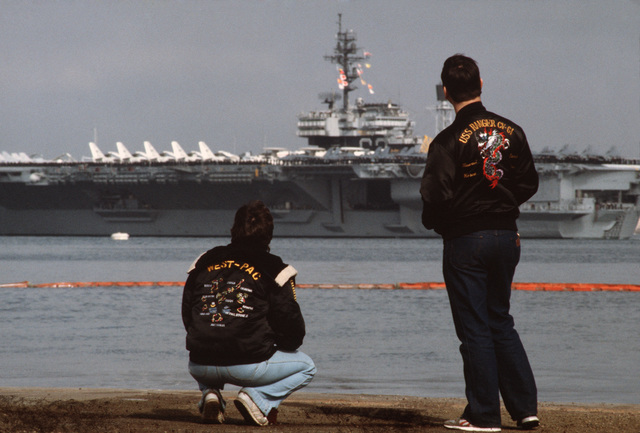 Two Sailors on the waterfront in street dress watch the aircraft carrier USS KITTY HAWK (CV 63) leaves its Pacific home port for the last time, after which it will report to the US Atlantic Fleet