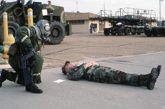 Staff Sergeant (SSGT) Ricky L. Wood, wearing chemical/biological warfare gear, kneels over a simulated casualty during an operational readiness exercise