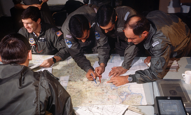 Captain (CPT) Jose Figueira, CPT Jose Henriques and Major (MAJ) Jorge Andrade, flight officers with the Portugese 501st Tactical Squadron, review routes that their squadron will fly in conjunction with the 37th Tactical Airlift Squadron (TAS). The 37th TAS is participating in its first deployment to Portugal