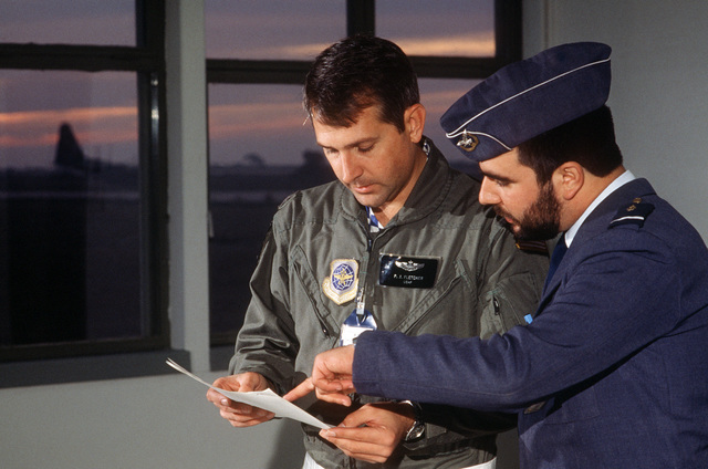 Major (MAJ) Paul Fletcher, 37th Tactical Airlift Squadron (TAS) mission commander, discusses the weather forecast with Lieutenant (LT) Carlos Batista, weather officer at Air Base 6. The 37th TAS is participating in its first deployment to Portugal
