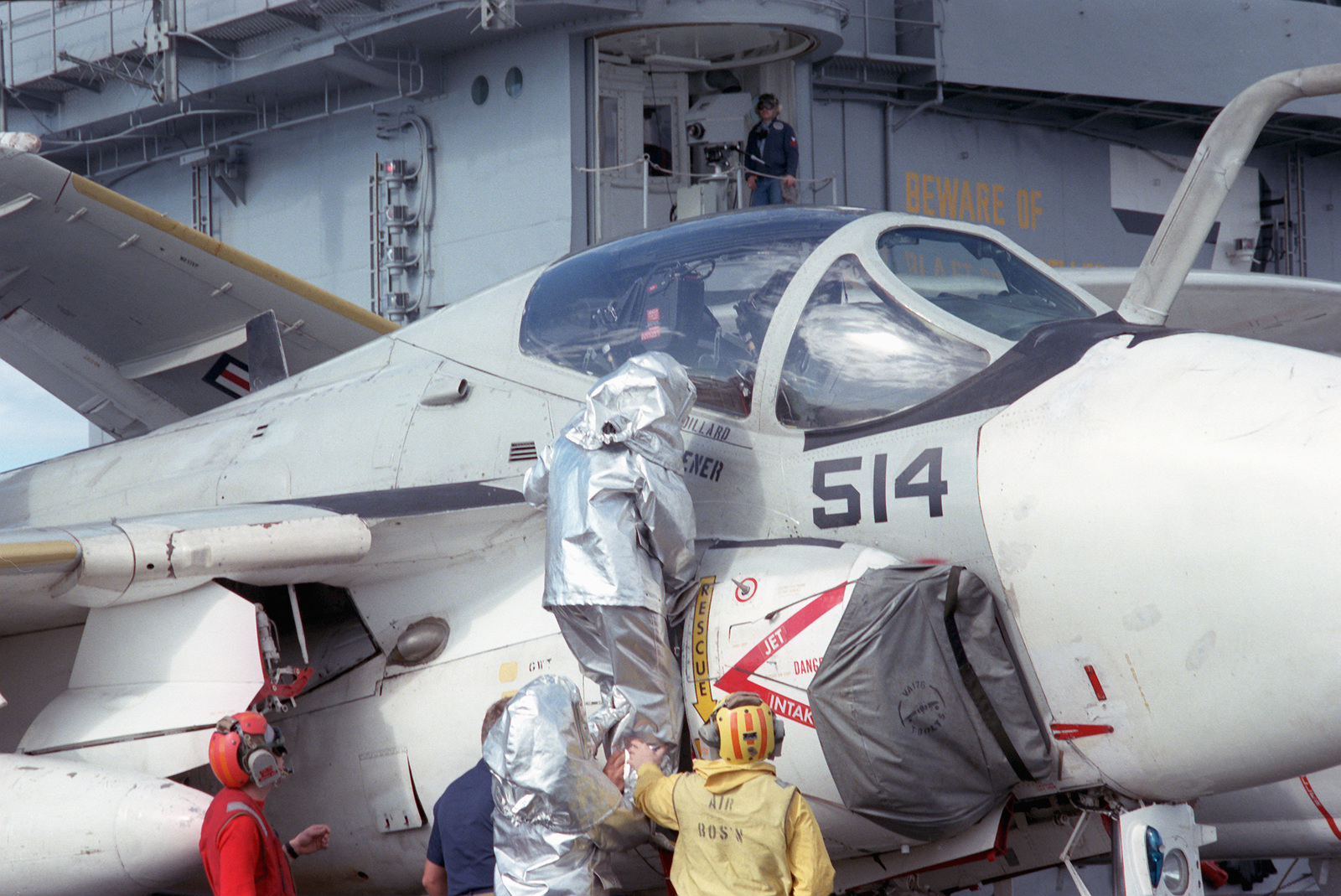 A firefighter wearing a proximity suit climbs onto an A-6E Intruder aircraft during a general quarters drill aboard the nuclear-powered aircraft carrier USS THEODORE ROOSEVELT (CVN 71)