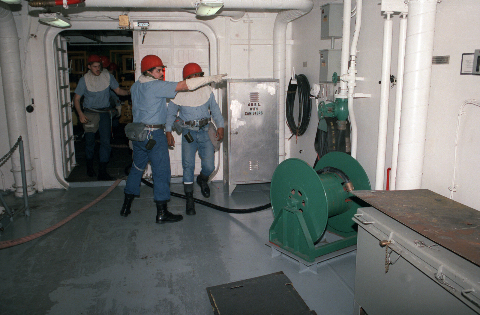 Members of a damage control party fight a simulated fire in a workspace aboard the nuclear-powered aircraft carrier USS THEODORE ROOSEVELT (CVN 71).  The ROOSEVELT is undergoing readiness testing during post-commissioning sea trails