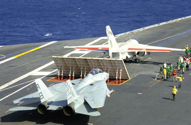 An S-3A Viking aircraft stands ready for launch as an F-14A Tomcat aircraft waits behind a blast deflector on the flight deck of the nuclear-powered aircraft carrier USS THEODORE ROOSEVELT (CVN-71). The pilots, who are from Carrier Air Wing 1 (CVW-1), are working toward their carrier qualifications. CVW-1 is the wing assigned to the aircraft carrier USS AMERICA (CV-66)