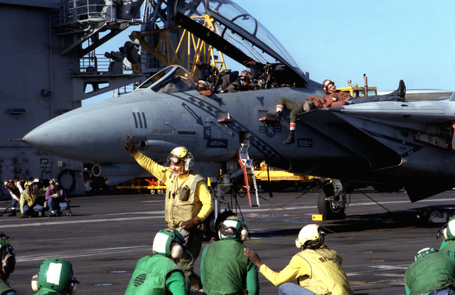 Members of a flight deck fire party practice on an F-14A Tomcat aircraft of Fighter Squadron 102 (VF-102), which is qualifying aboard the nuclear-powered aircraft carrier USS THEODORE ROOSEVELT (CVN 71)