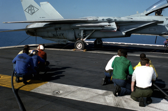 Members of a flight deck fire party train a hose on an F-14A Tomcat aircraft of Fighter Squadron 102 (VF-102), during a general quarters drill aboard the nuclear-powered aircraft carrier USS THEODORE ROOSEVELT (CVN 71). The Tomcat's squadron is qualifying aboard CVN-71)