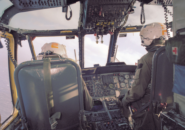 The pilot and copilot man their stations in the cockpit of an SH-3 Sea King helicopter